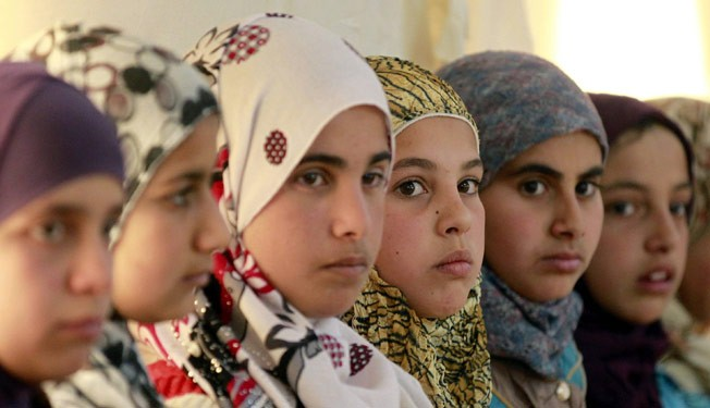 "Syrian refugee girls sit at the United Nations Children's Fund (UNICEF) ""Child Friendly Spaces"" (CFSs) in the Zaatari refugee camp, near the Jordanian border with Syria, on March 8, 2014."