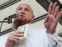 Islamic cleric Pierre Vogel gestures as he delivers his speech during a pro-Islam demonstration in Hamburg July 9, 2011. The book he is holding is a German edition of the Koran. REUTERS/Morris Mac Matzen