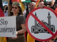 "Demonstrators display signs with crossed mosques during a protest in front of a mosque in Berlin, Germany, Saturday, Aug. 18, 2012. A Berlin court had allowed the demonstration of the far-right group ' Pro Deutschland'  held under the slogan ""Islam does not belong in Germany — stop Islamization.""  (AP Photo/Gero Breloer)"