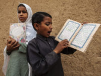 A girl standing in for her teacher supervises a lesson while a boy recites from a book at a school in a slum on the outskirts of Islamabad October 11, 2013. REUTERS/Zohra Bensemra (PAKISTAN - Tags: EDUCATION SOCIETY POVERTY) - RTX14721