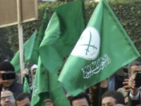 Gaza's Hamas Prime Minister Ismail Haniyeh, flashes the victory sign as he visits the leader of Egypt's Muslim Brotherhood, Mohammed Badie in Cairo, Egypt, Monday, Dec. 26, 2011. The green flags represent the Muslim Brotherhood. (AP Photo/Mohammed Abu Zaid)