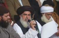 Pakistani head of the Tehreek-i-Labaik Yah Rasool Allah Pakistan (TLYRAP) religious group Khadim Hussain Rizvi (C) announces the end of sit-in protest on a blocked flyover bridge during a press conference in Islamabad on November 27, 2017. The Islamist leader whose group clashed violently with Pakistani security forces and paralysed Islamabad for weeks called off the sit-in protest November 27 after the law minister resigned, meeting its key demand. / AFP PHOTO / AAMIR QURESHI