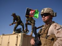 """In this photograph taken on August 28, 2017, a US Marine looks on as Afghan National Army soldiers raise the Afghan National flag on an armed vehicle during a training exercise to deal with IEDs (improvised explosive devices) at the Shorab Military Camp in Lashkar Gah in Helmand province. Marines in Afghanistan's Helmand say Donald Trump's decision to keep boots on the ground indefinitely gives them """"all the time in the world"""" to retake the province, once the symbol of US intervention but now a Taliban stronghold. They may need it. At the hot, dusty Camp Shorab, where many of the recently deployed Marines train their Afghan counterparts in flat, desert terrain, the Afghans admit their army still cannot fight alone.   / AFP PHOTO / WAKIL KOHSAR        (Photo credit should read WAKIL KOHSAR/AFP via Getty Images)"""